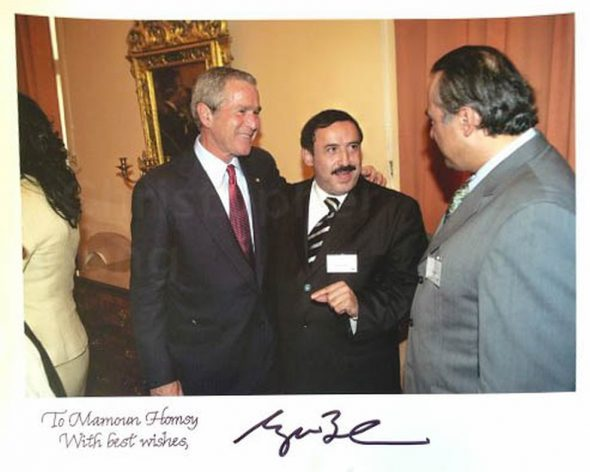 Former Syrian parliamentarian Mohamed-Mamon Alhomsi and former U.S. president George W. Bush in Prague in 2007. The photo, a gift from Bush to Alhomsi, is signed by Bush. Courtesy of Mohamed-Mamon Alhomsi.