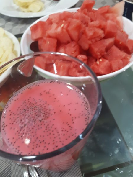 Sweet and aromatic drink made out of syrup , water & milk with basil seeds, watermelon in plate