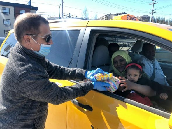 Monzur Choudhury hands out goodie bags to a local family on Sunday. Within the first hour of the Eid event, over 40 cars had driven by to pass along holiday greetings and collect the treats. (Danielle d'Entremont/CBC)