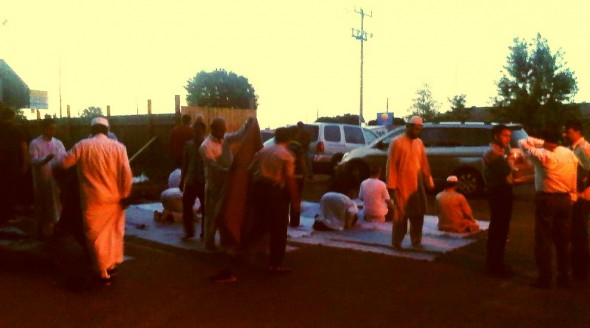 Brothers begin folding U-Hall Moving blankets as Sunnah Prayers performed after Maghrib, Saturday July 13 2013