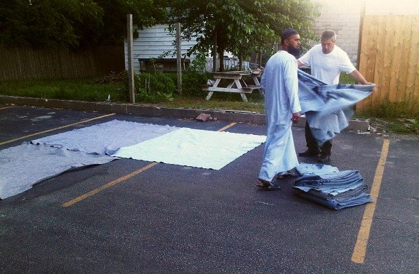 Hassan and Bilal spread U-Haul moving blankets as Chatham Maghrib Prayer space - Saturday July 13 2013