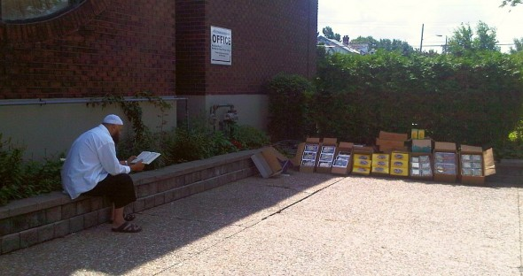 12 - Vendor reads Qur'an beside his merchandise, before Jumah Prayers, Ottawa Main Mosque, Jumah Friday August 2 2013