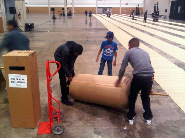 07 - Cardboard Prayer Mat Rolls being unrolled inside Direct Energy Centre for Eid Al Adha prayers IMG-20131015-42445