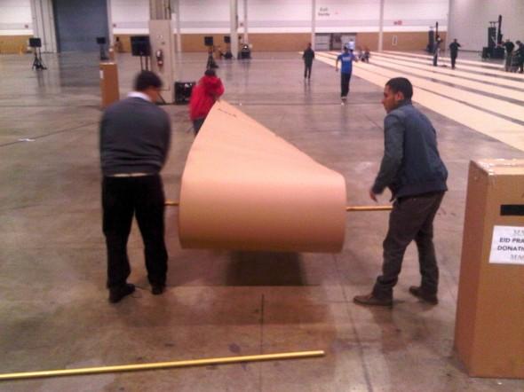 08 - Cardboard Prayer Mat Rolls being unrolled inside Direct Energy Centre for Eid Al Adha prayers IMG-20131015-42446