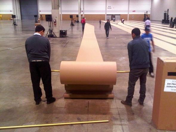 09 - Cardboard Prayer Mat Rolls being unrolled inside Direct Energy Centre for Eid Al Adha prayers IMG-20131015-42448